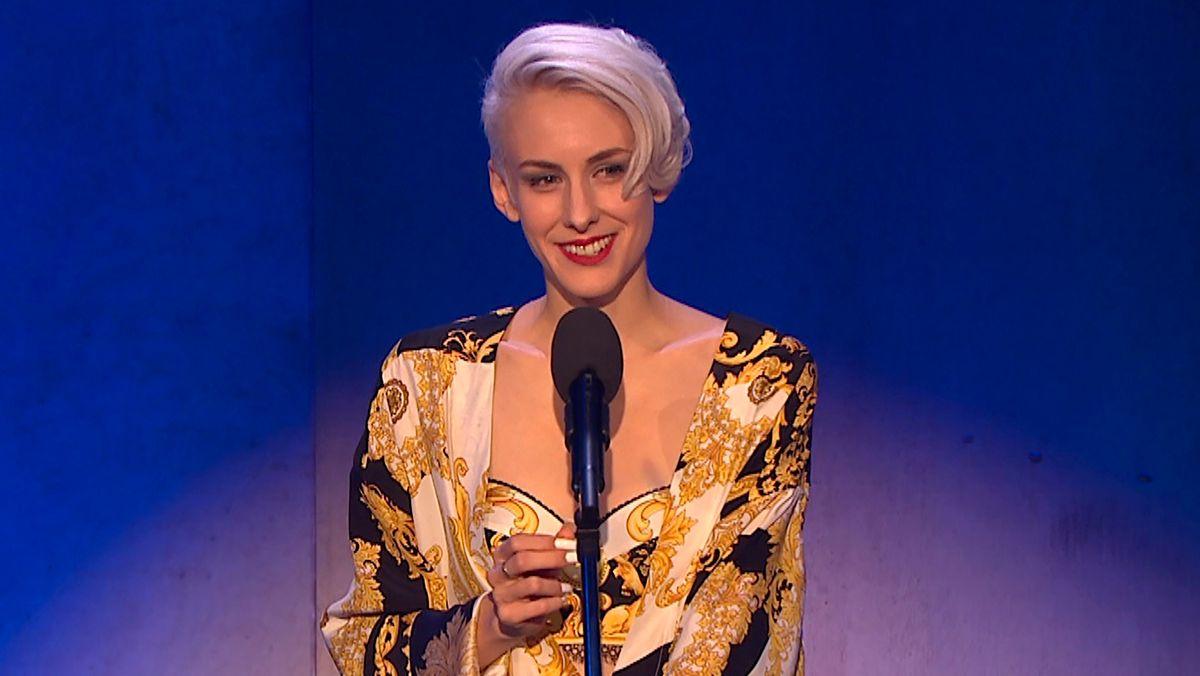 Eine lächelnde Frau mit Wasserstoffweißer Stirnlocke redet ins Mikrofon