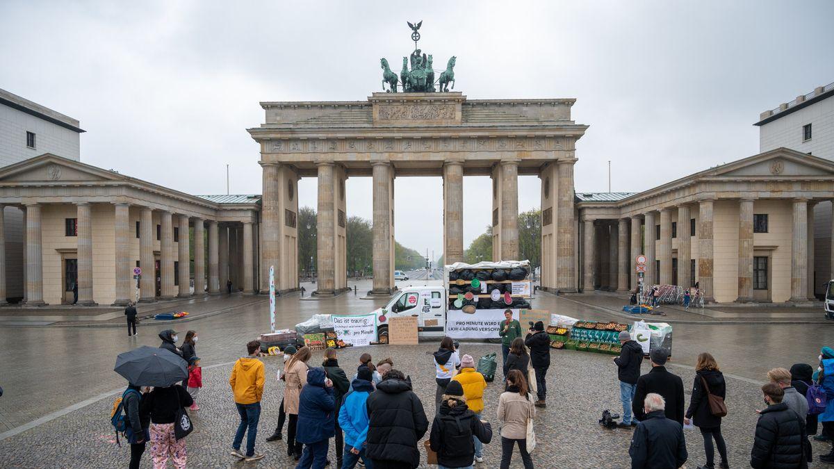 Menschen, LKW und Lebensmittel vor dem Brandenburger Tor in Berlin bei Regen.