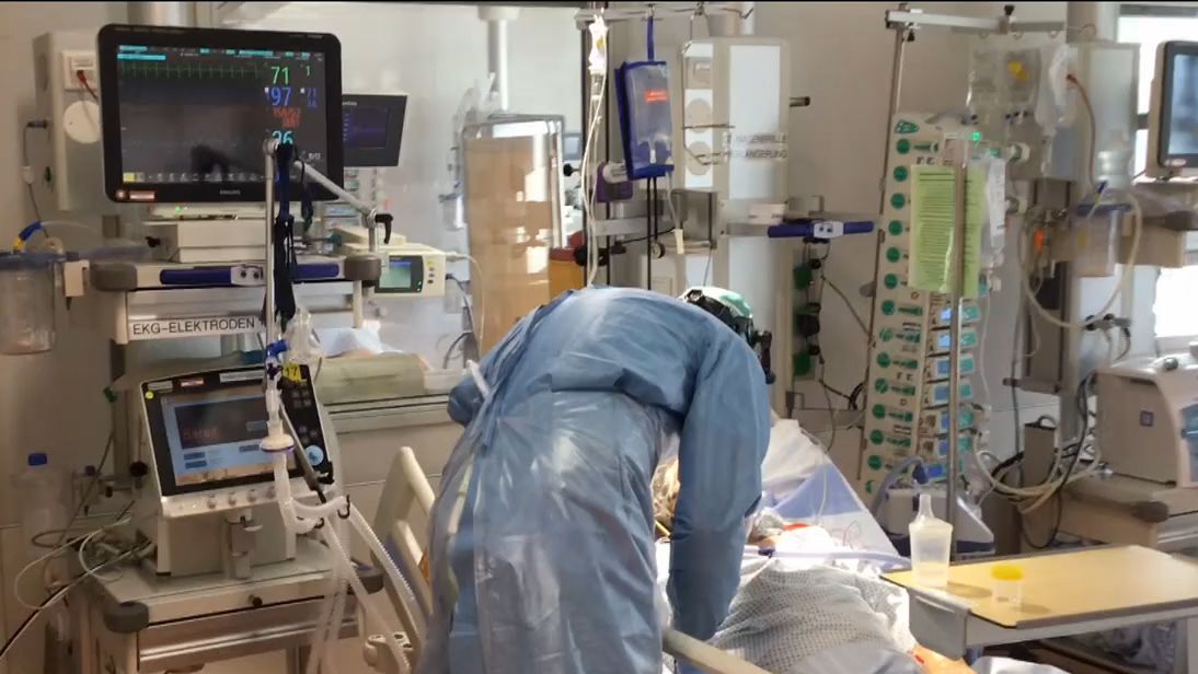 Ein Arzt im blauen Kittel beugt sich über das Bett eines Intensivpatienten