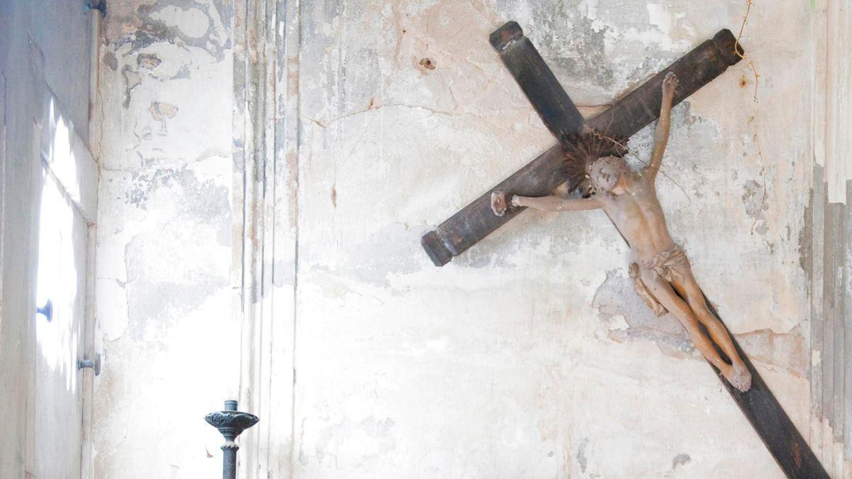Ein Kreuz hängt schief in einer verlassenen Kapelle