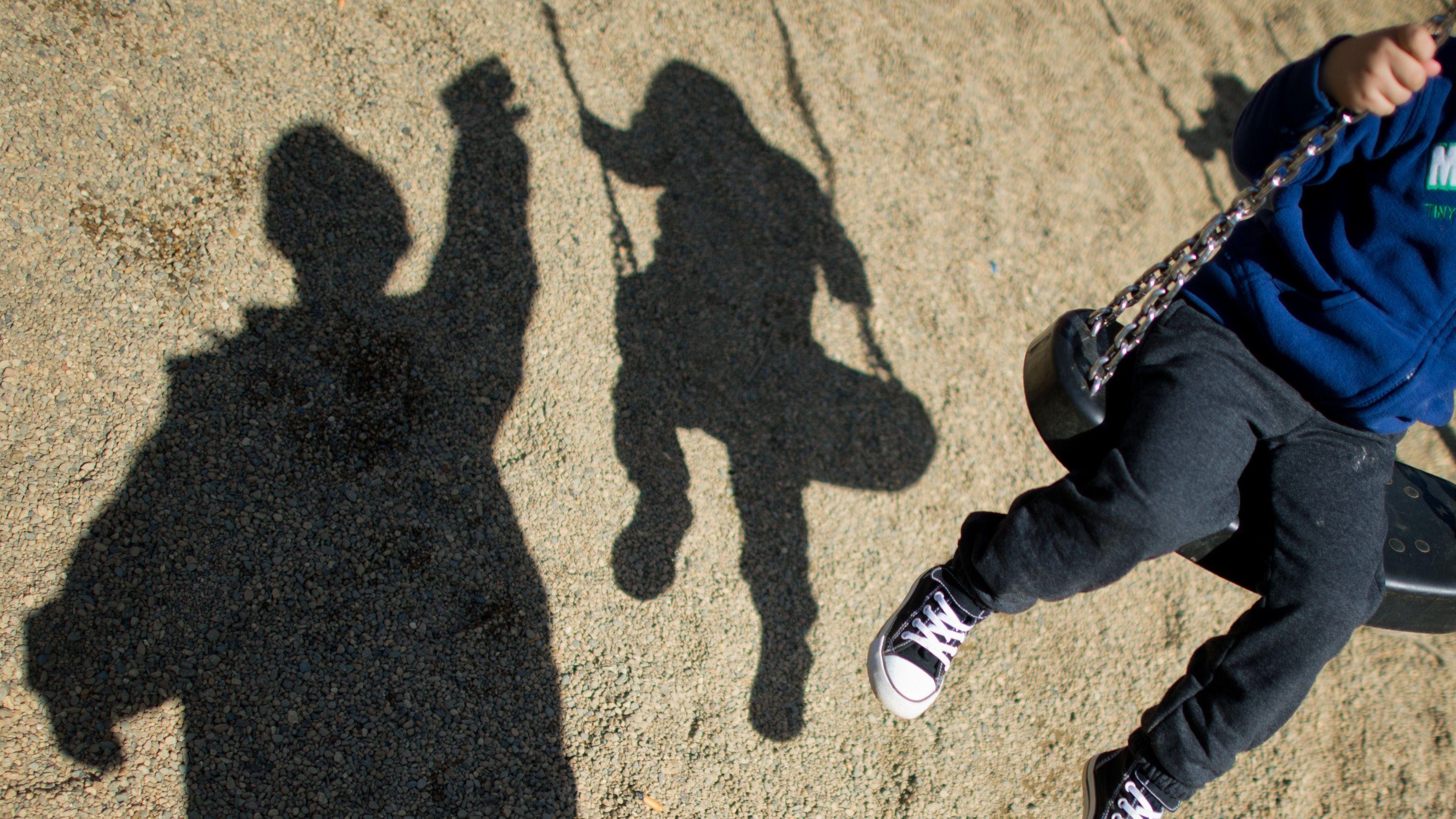 Ein Kind auf einer Schaukel neben dem Schatten eines Mannes (Symbolbild)