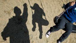 Ein Kind auf einer Schaukel neben dem Schatten eines Mannes (Symbolbild) | Bild:pa / dpa / Julian Stratenschulte