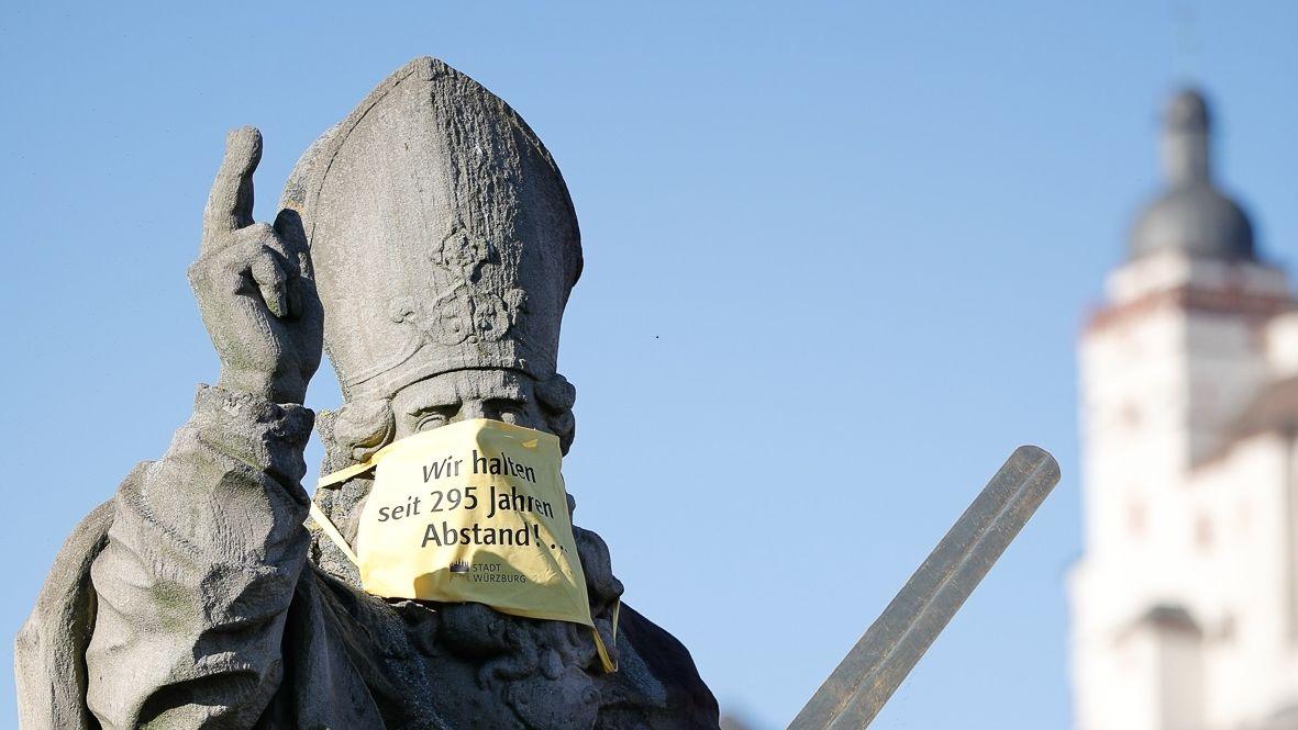 Der heilige Kilian mit Mund-Nase-Maske auf der Alten Mainbrücke
