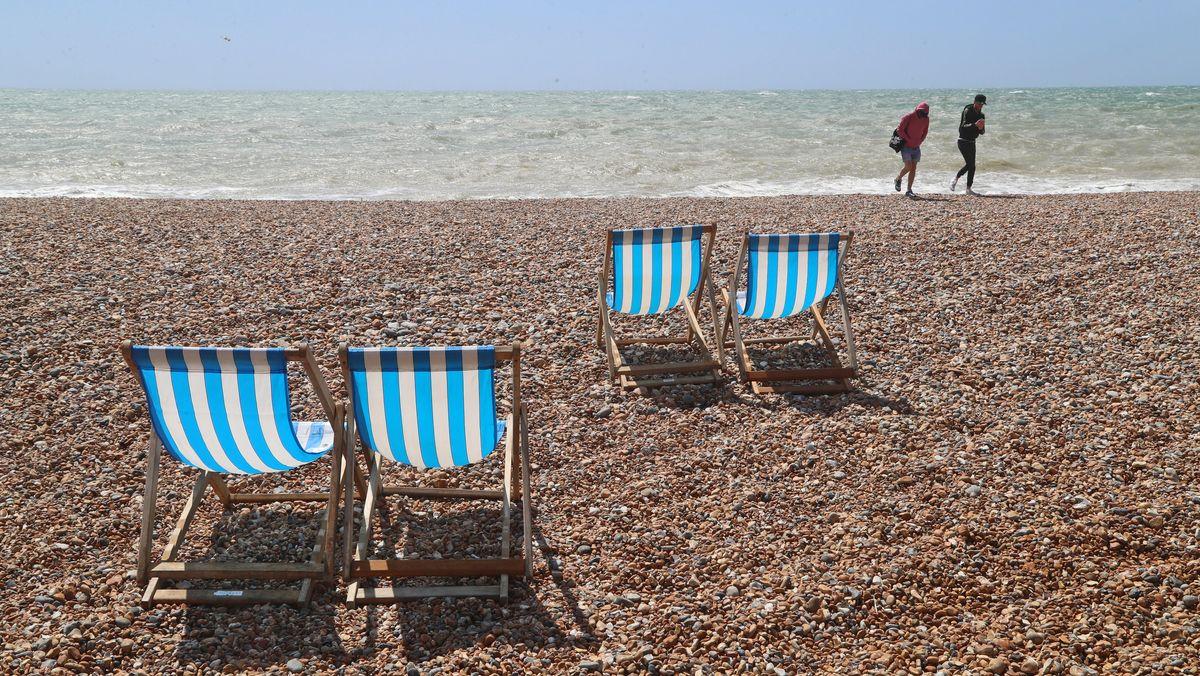 Zwei Menchen am Strand. Im Vordergrund befinden sich zwei Liegen.