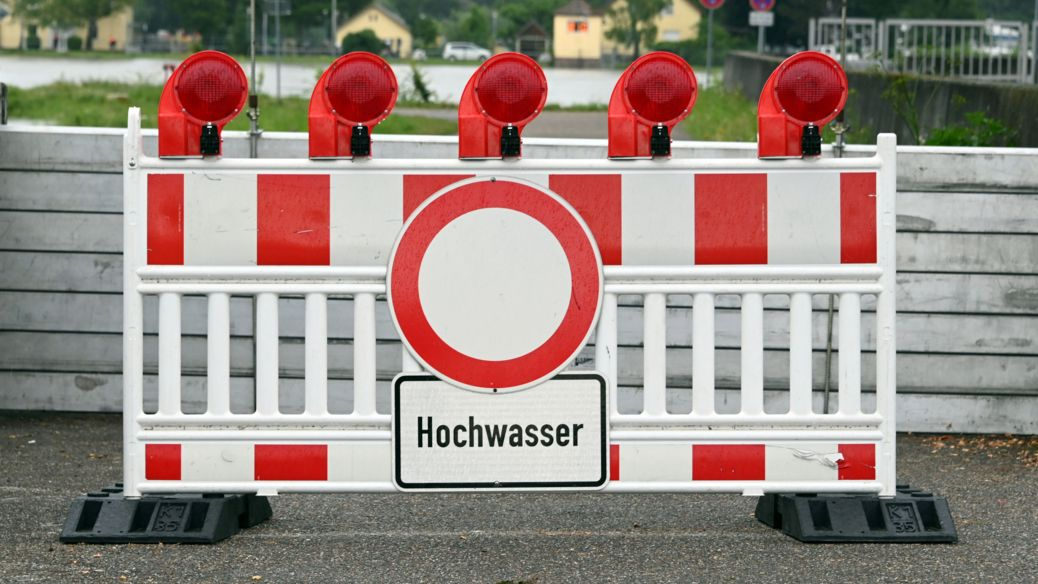 """Ein Weg ist abgesperrt mit dem Hinweisschild """"Hochwasser""""."""