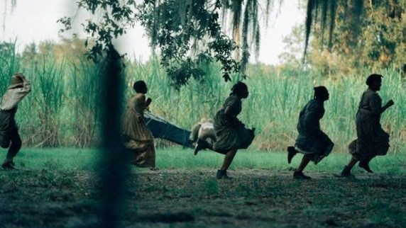 Man sieht fünf Afroamerikanerinnen an einem Feld entlang laufen.
