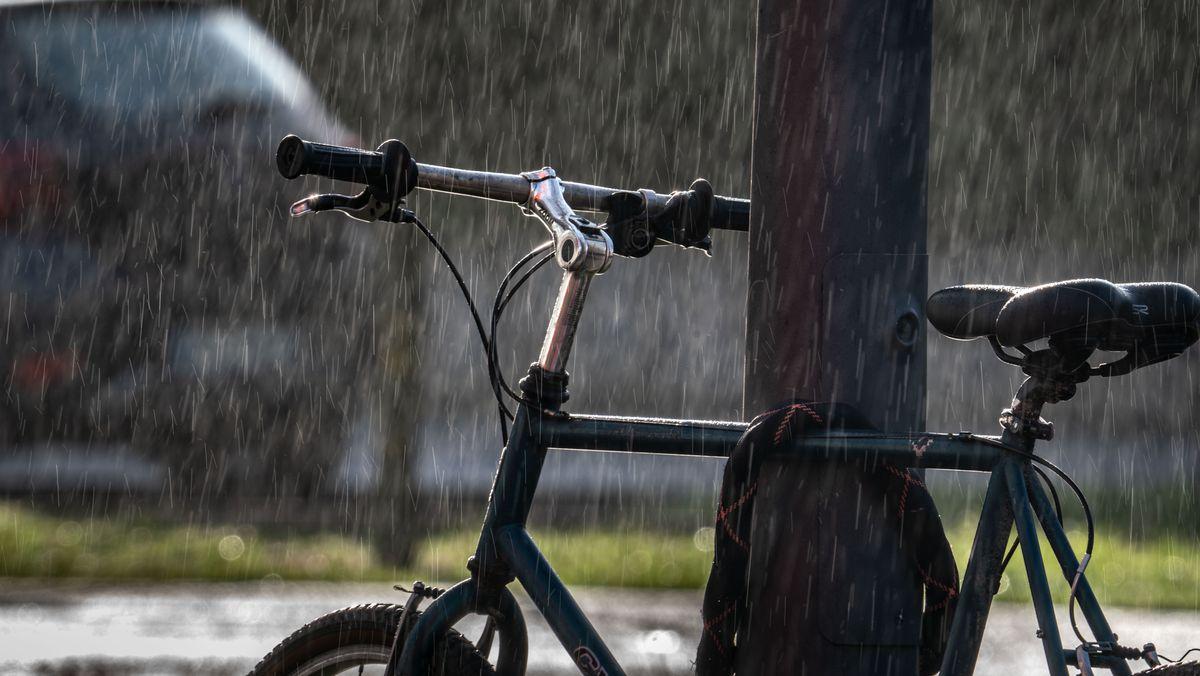 Ein Fahrrad steht im Regen und wird gleichzeitig von der Sonne angestrahlt (Symbolbild).