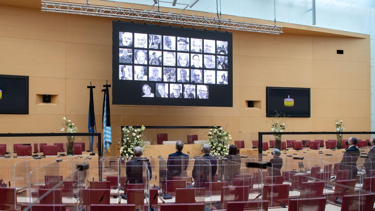 Die Teilnehmer des Trauerakts für die Corona-Verstorbenen in Bayern stehen im bayerischen Landtag während einer Schweigeminute.