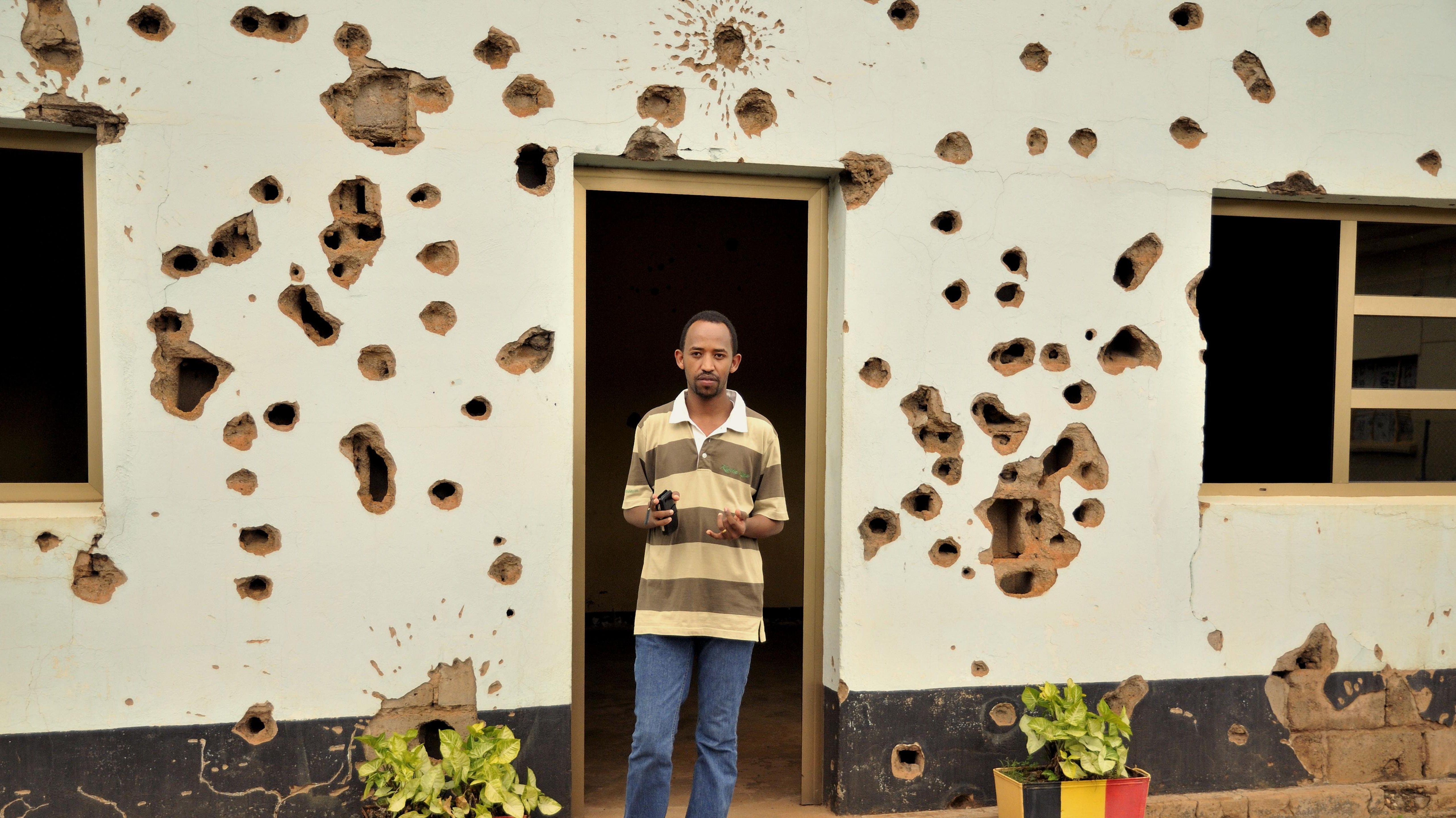 Ortskundiger Führer in der Gedenkstätte für die im April 1994 ermordeten belgischen Blauhelm-Soldaten in Kigali, Ruanda, Afrika - steht im Eingang eines Hauses, das von großen Einschusslöchern überzogen ist, die Fenster haben keine Scheiben mehr.
