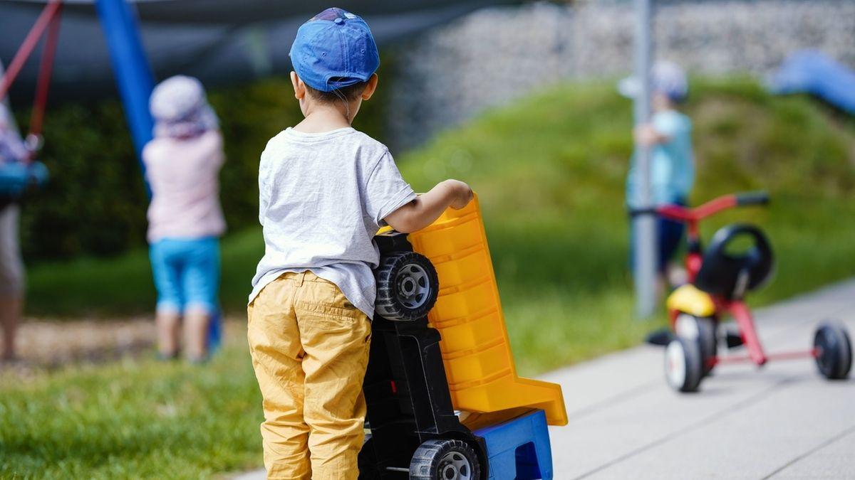 Ein Kind spielt in einer Kindertagesstätte mit einem Plastikfahrzeug.