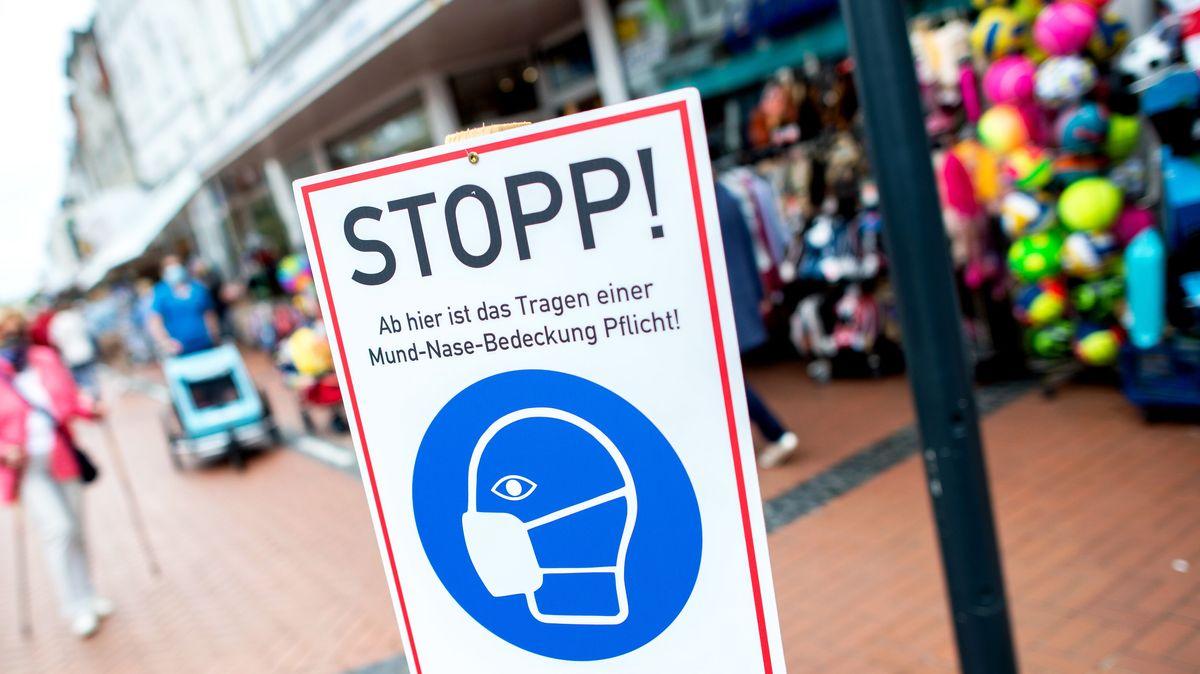 """Ein Schild mit der Aufschrift """"Stopp! Ab hier ist das Tragen einer Mund-Nasen-Bedeckung Pflicht!"""" steht in einer Fußgängerzone."""
