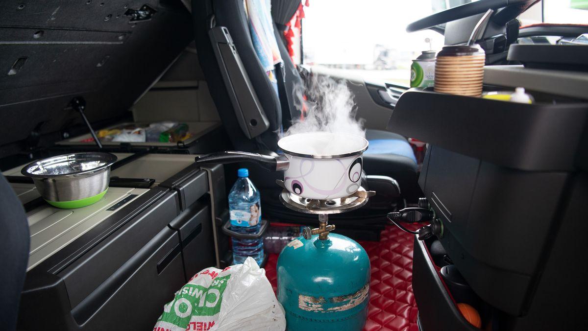 Aus einem Topf, der in der Fahrerkabine eines Lastwagens auf einem Gaskocher steht, steigt Dampf