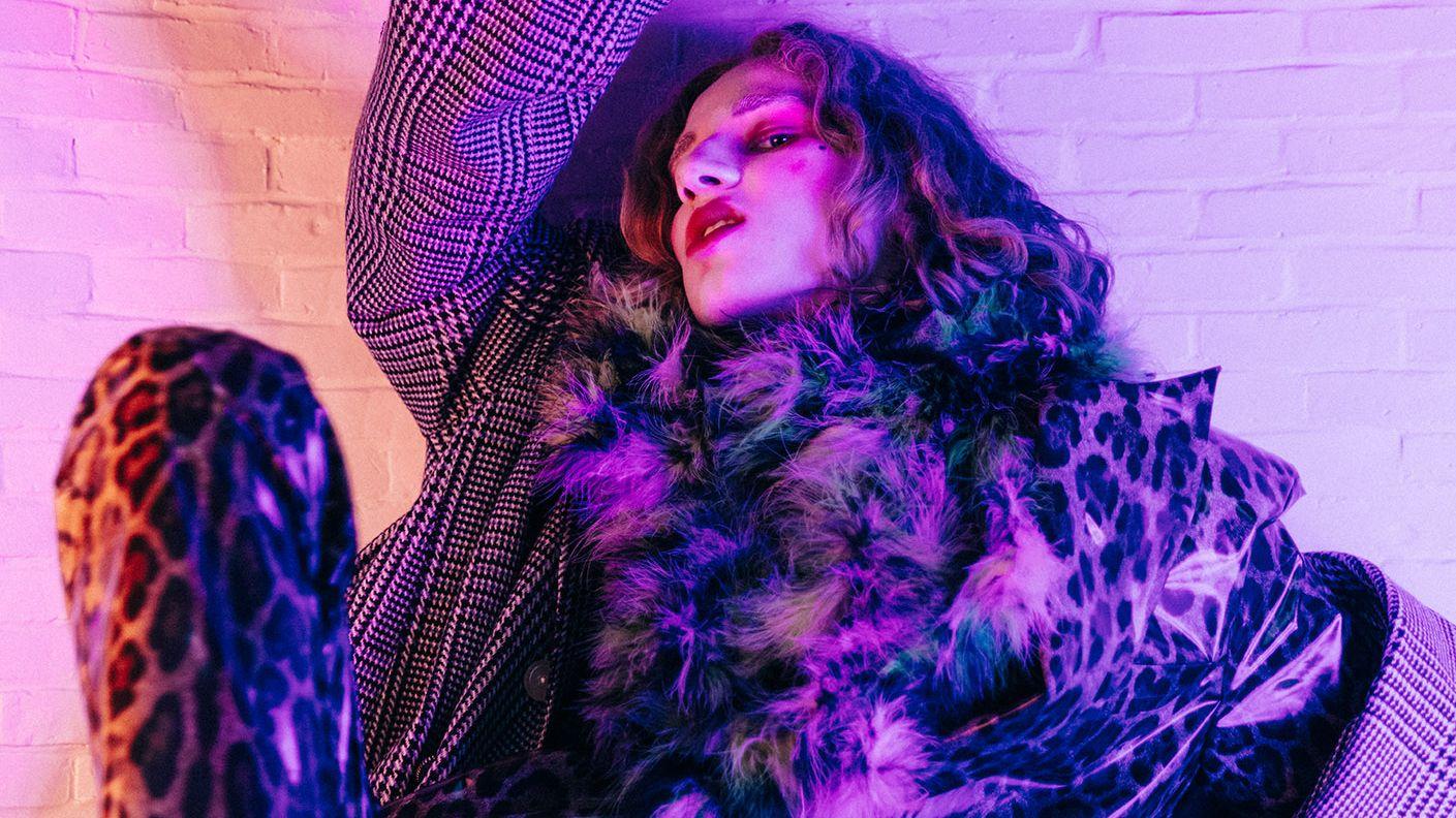 Ein Model trägt einen Anzug aus einem beschichteten Stoff in Leopardenoptik. Darüber einen Mantel und einen sehr flauschigen Schal. Das Model sitzt gegen eine Wand gelehnt.
