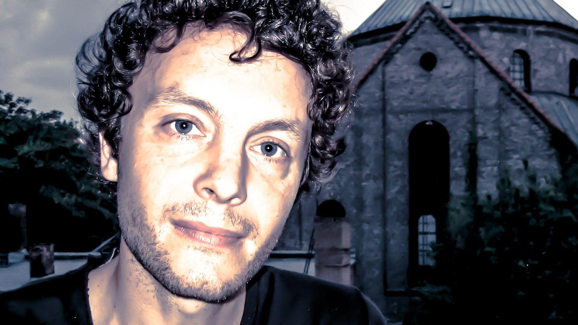 Sehr nah aufgenommenes Porträtfoto von Schriftsteller Thomas Klupp, im Hintergrund ist eine Kirche zu sehen