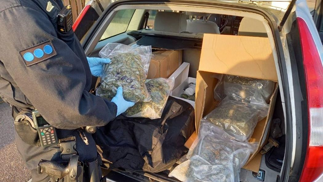 Bild vom Polizeibeamten mit Rauschgift im Kofferaum