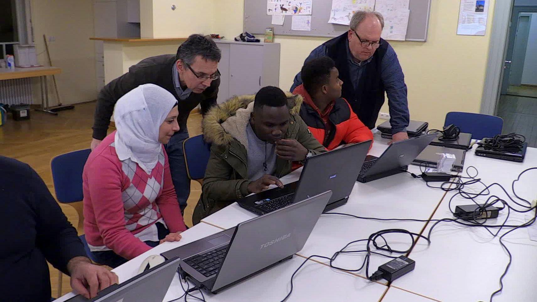 Mitglieder der Computerspende Regensburg erklären neuen Laptop-Besitzern die Geräte