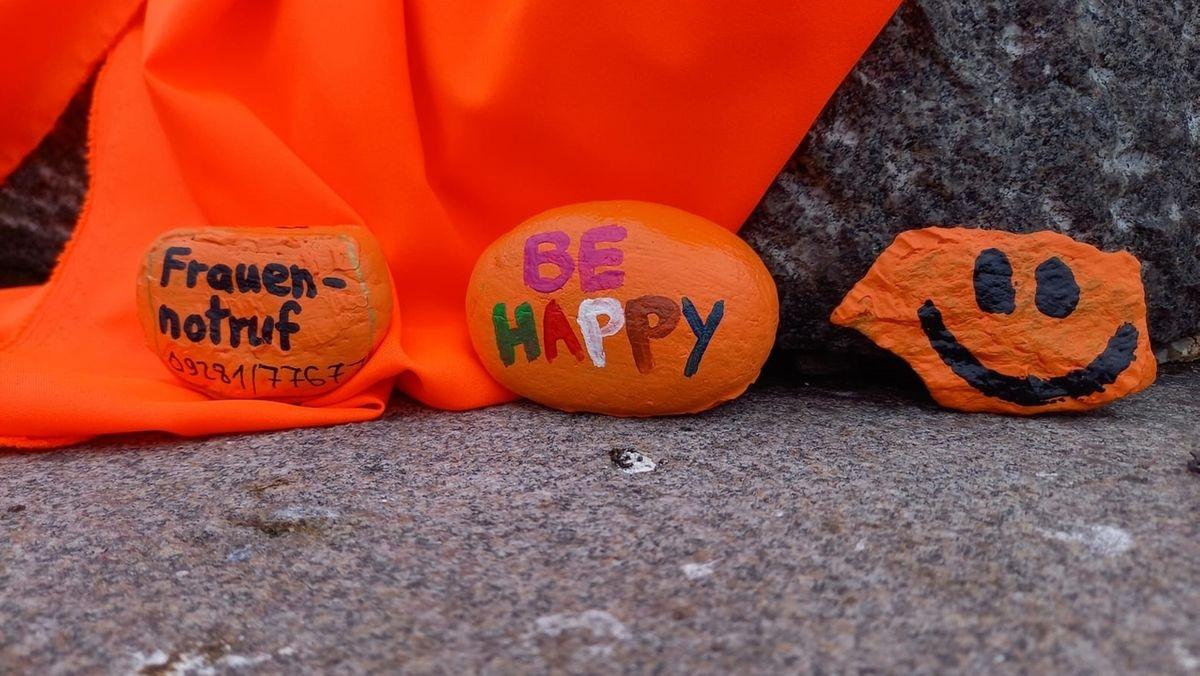 """Orange angemalte Steine mit der Aufschrift """"Frauennotruf"""" und """"Be Happy"""" liegen am Boden, dahinter hängt eine orangefabene Stoffbahn."""