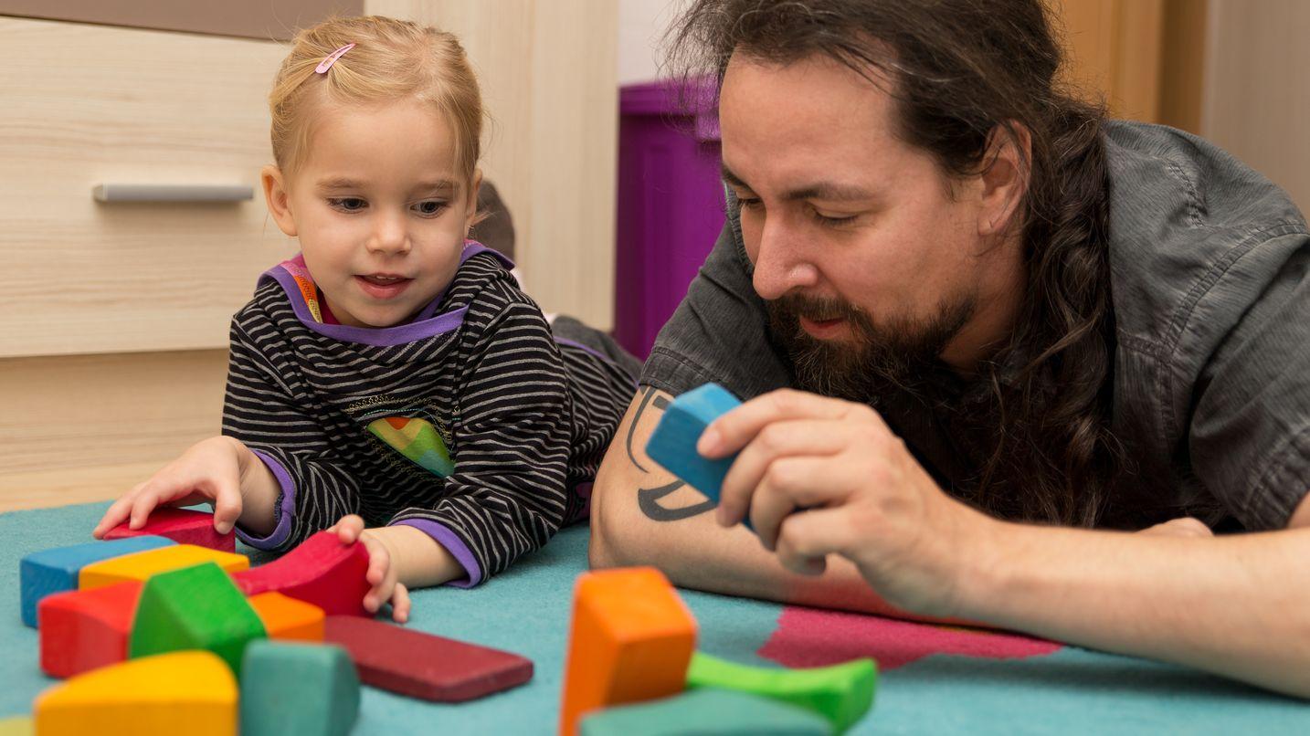 Vater spielt mit seinem Kind Bauklötze stapeln