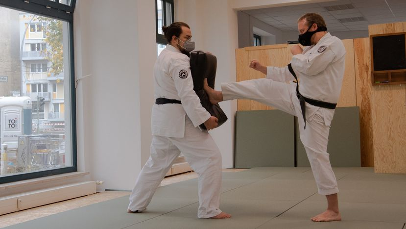 Zwei Mitglieder einer Kampfsportschule trainieren mit Maske im Übungsraum