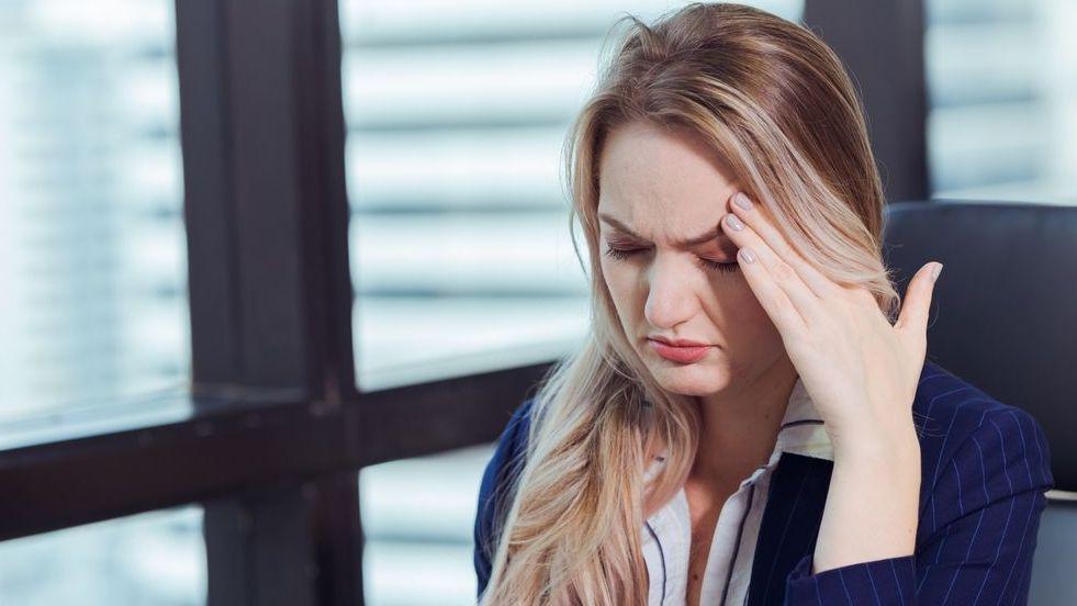 Frau die sich mit schmerzverzerrtem Gesicht an den Kopf fasst