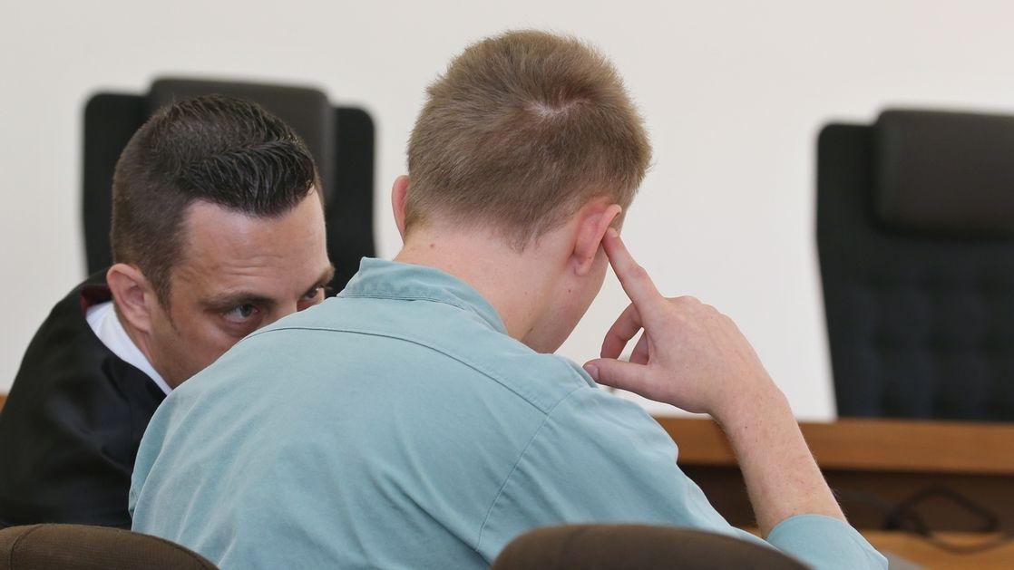 Der 22-Jährige Angeklagte sitzt im Landgericht neben seinem Rechtsanwalt.