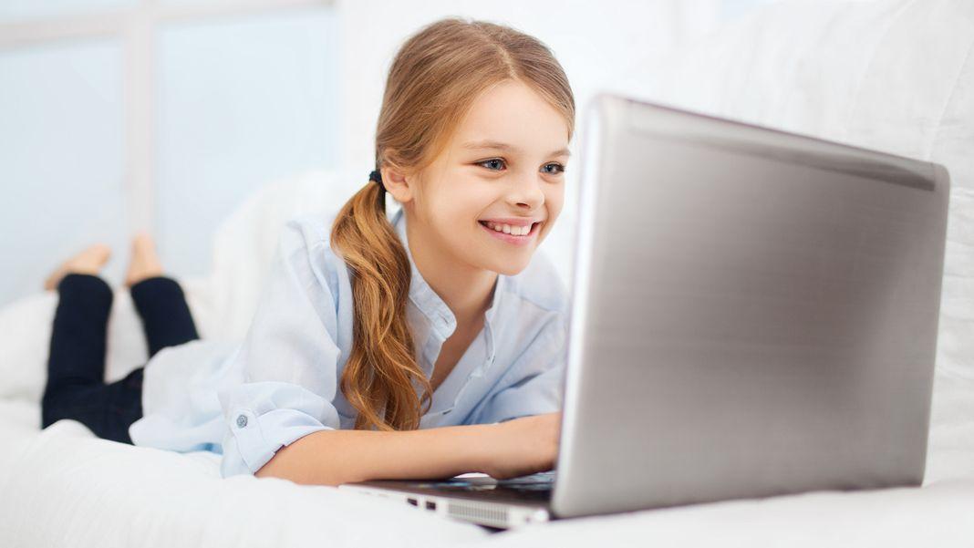 Ein Mädchen blickt lächelnd auf einen Laptop.