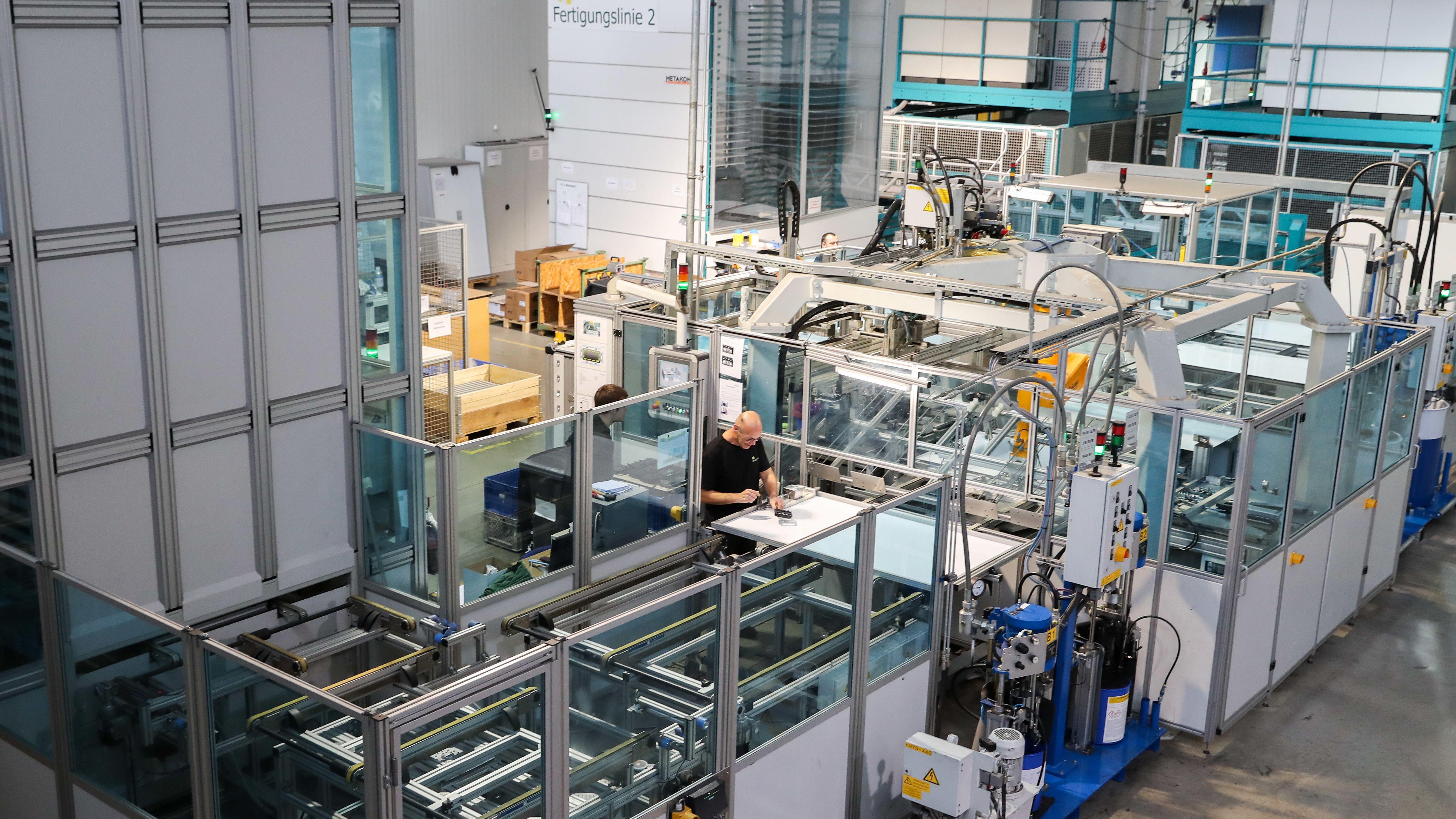 Ein Mitarbeiter der Heckert Solar GmbH arbeitet in der Fertigungslinie von Solarmodulen.