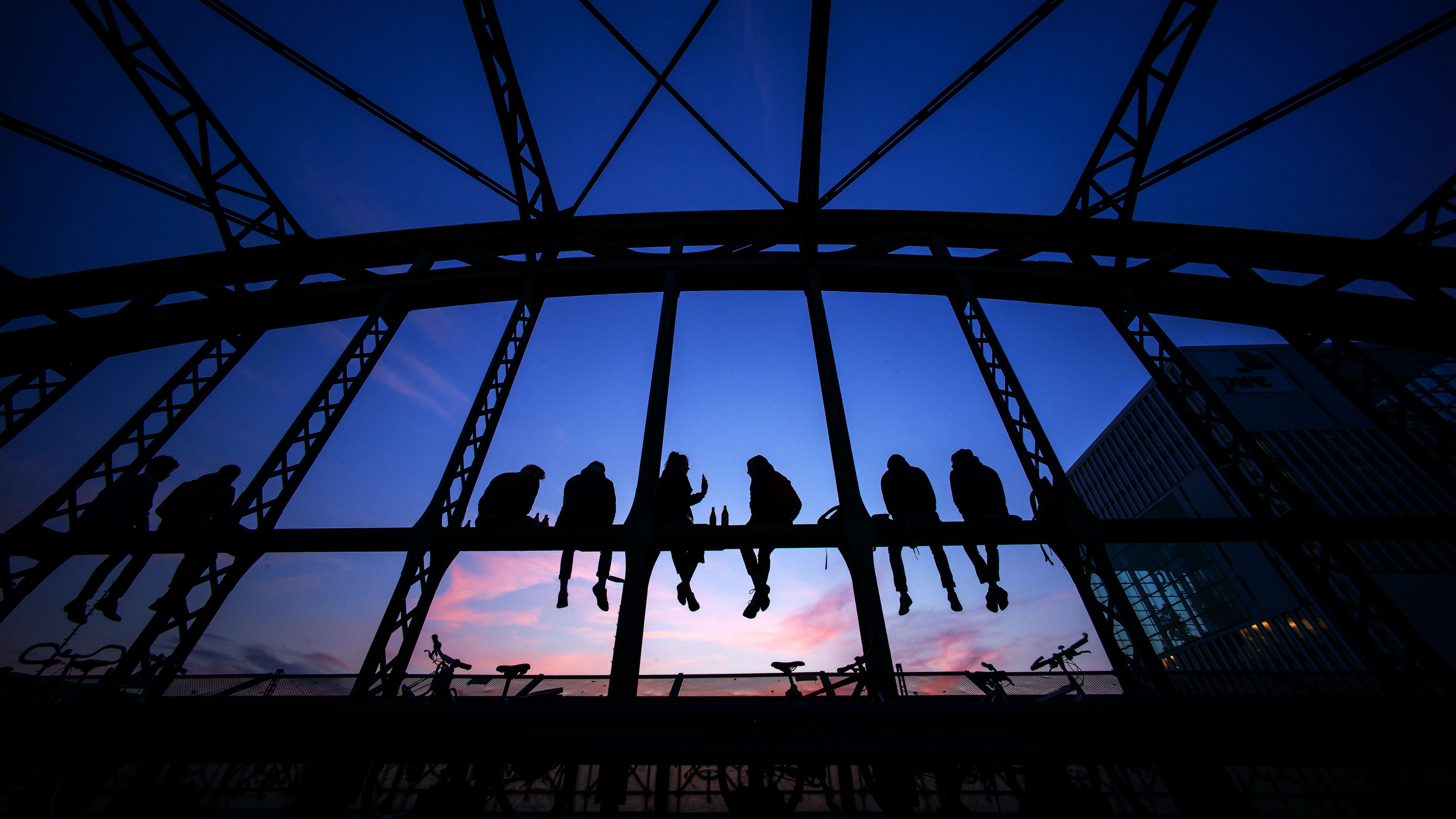 Symbolbild: Jugendliche sitzen am Abend auf den stählernen Querträgern der Hackerbrücke und beobachten den Sonnenuntergang am Horizont