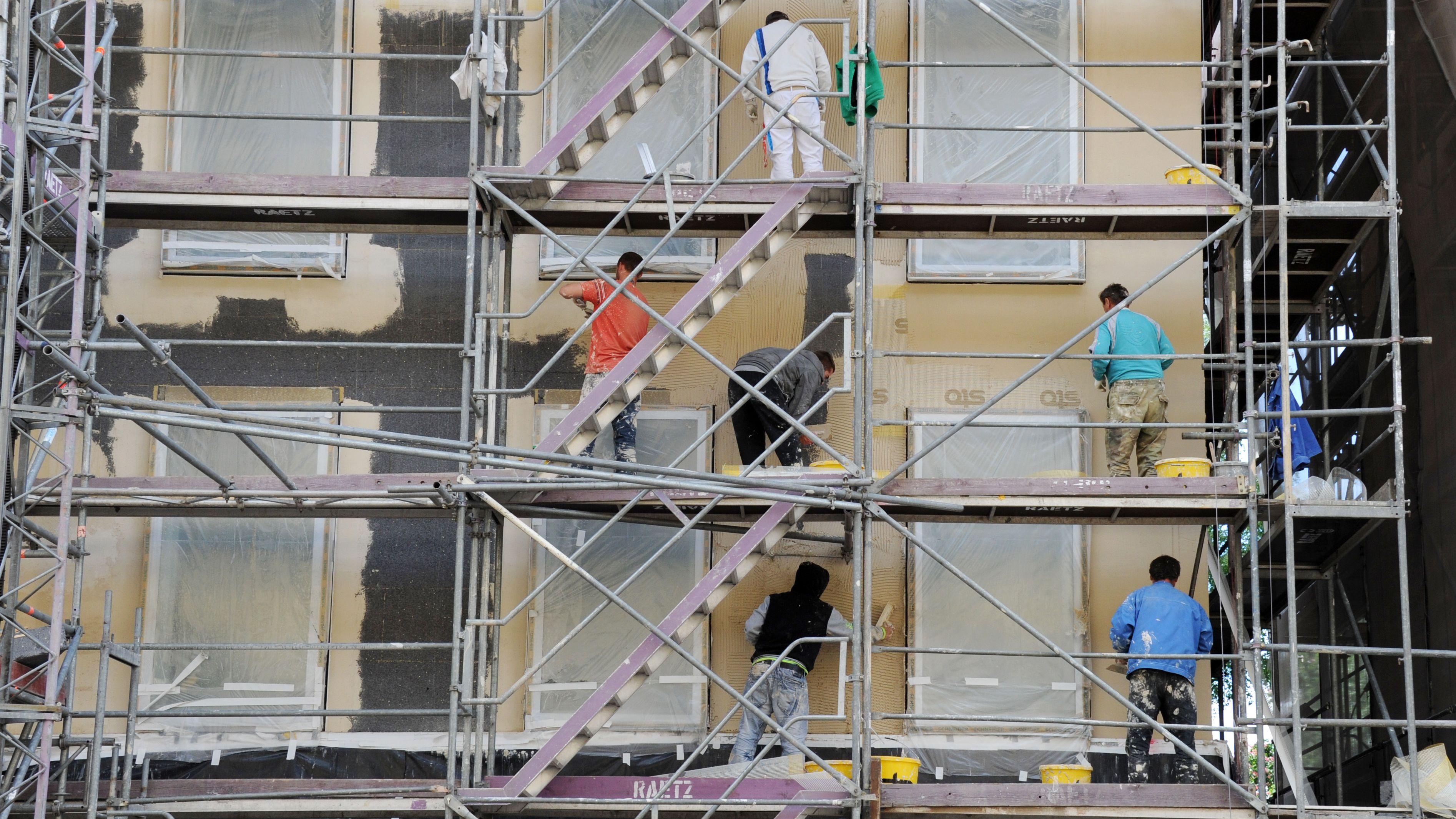 Bauarbeiter verputzen und verspachteln auf einer Baustelle in München eine Dämmschicht an der Aussenfassade eines Hauses.