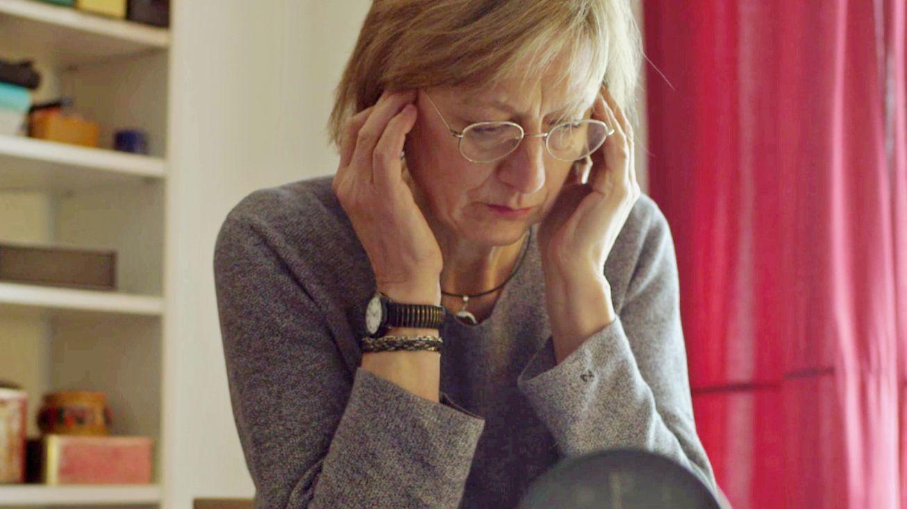 Eine Frau hält sich die Ohren zu