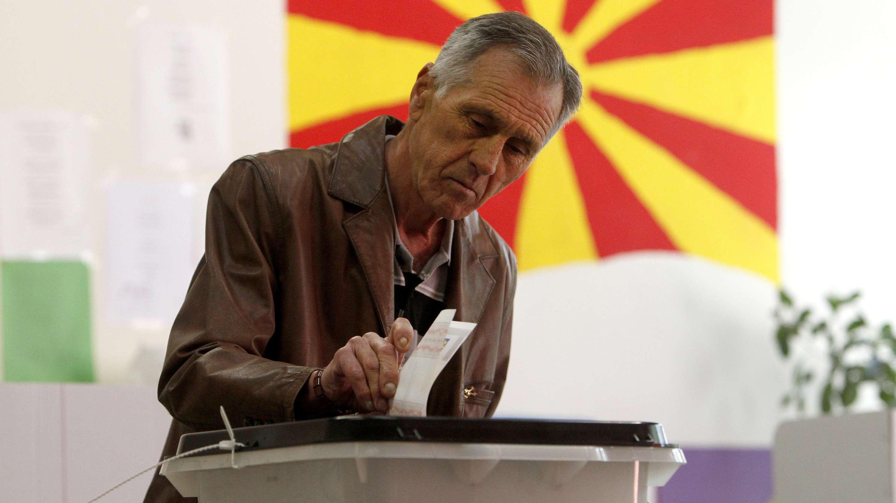 Ein Mann wirft in Nordmazedonien seinen Stimmzettel in die Wahliurne