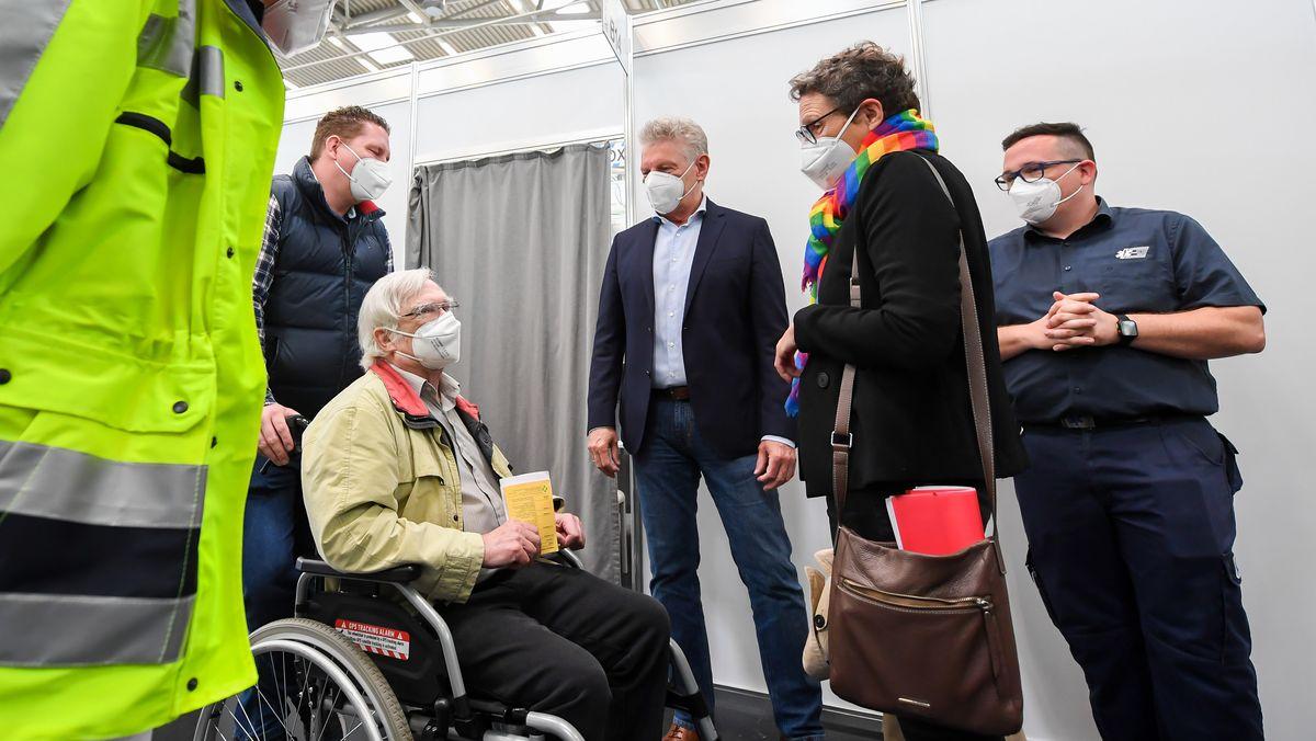 Oberbürgermeister Dieter Reiter und Gesundheitsreferentin Beatrix Zurek mit Dieter Buchner (70), der die 500.000 Impfung im Münchner Impfzentrum erhielt.