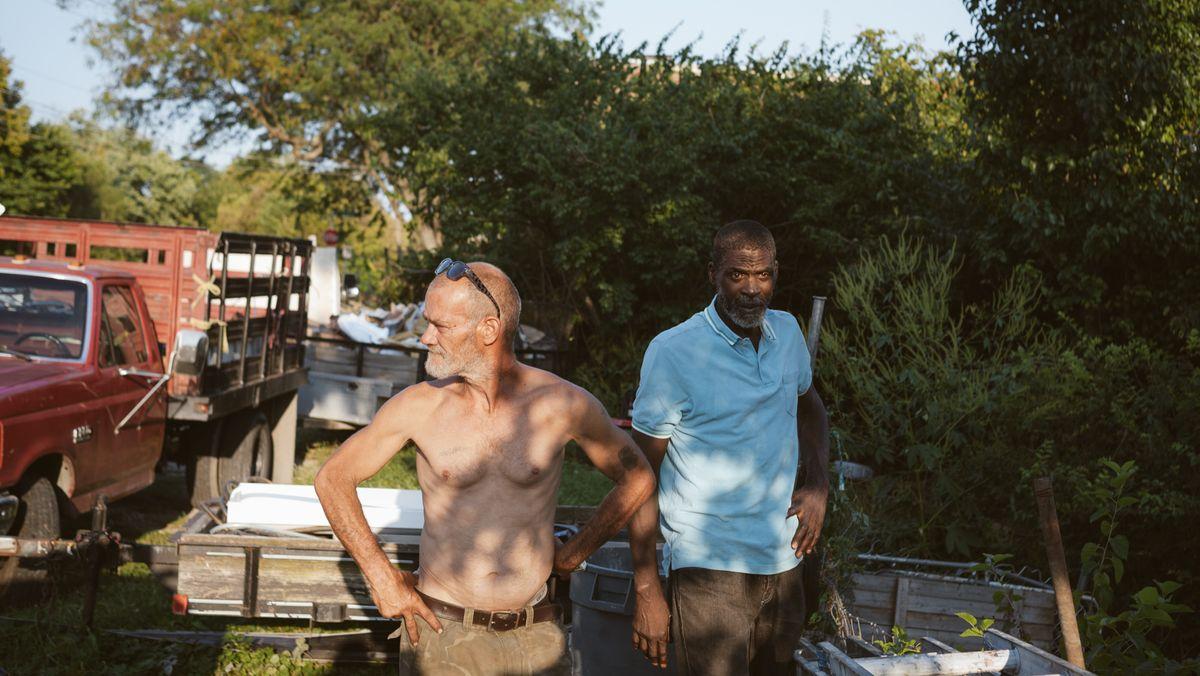 Zwei Männer stehen im Grünen auf einer Baustelle. Ein Truck im Hintergrund.