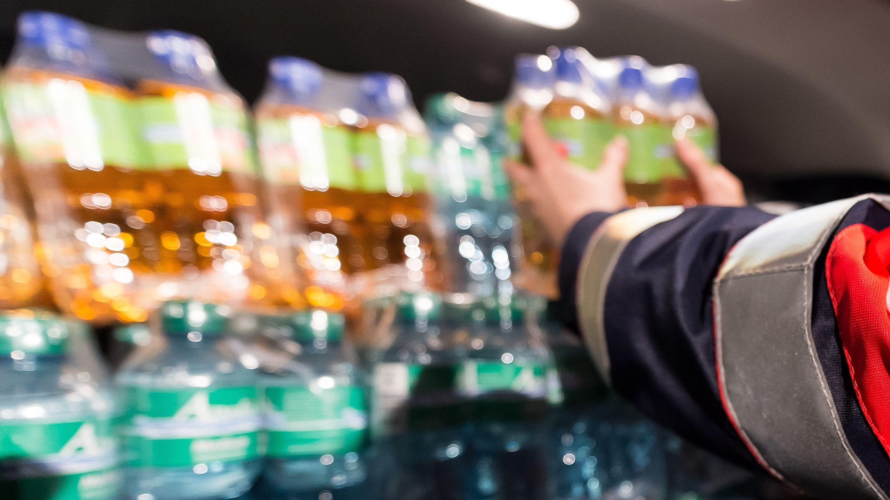 Symbolbild: Helfer verteilen Getränke an Autofahrer, die im Stau warten