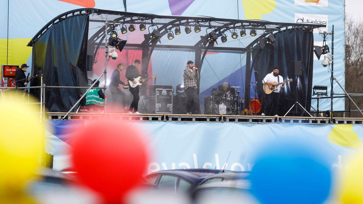 Musiker auf einer Open-Air-Bühne, statt Publikum parkende Autos