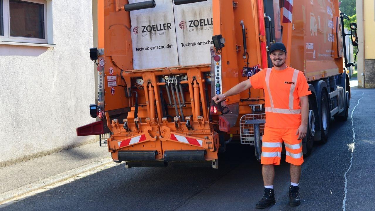 Ein Mitarbeiter steht neben einem orangen Müll-Lkw der Müllabfuhr im Landkreis Würzburg.