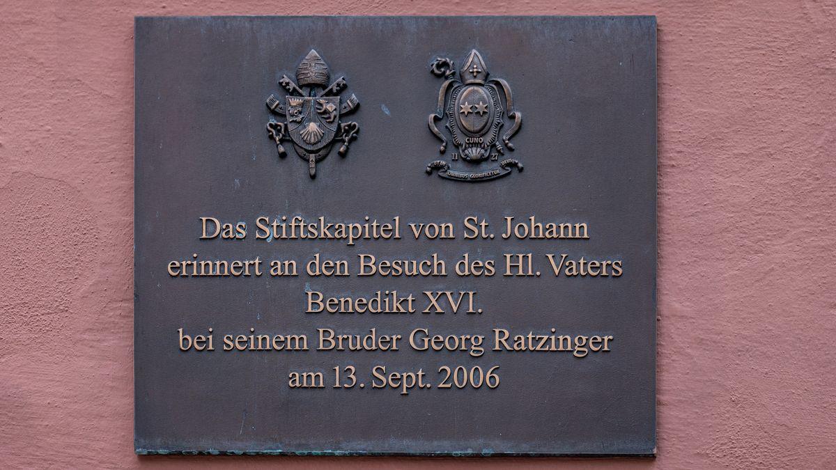 """Ein Schild mit der Aufschrift """"Das Stiftskapitel von St. Johann erinnert an den Besuch des Hl. Vaters Benedikt XVI. bei seinem Bruder Georg Ratzinger am 13. Sept. 2006"""" hängt am ehemaligen Wohnhaus von Georg Ratzinger in der Altstadt."""
