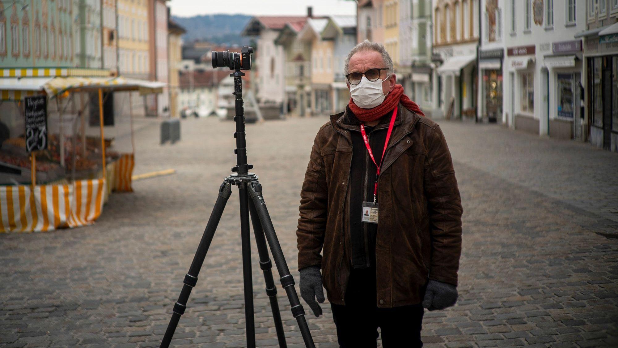 Ein Mann steht in einer verlassenen Fußgängerzone neben seinem Foto-Stativ. Er trägt eine Sonnenbrille und einen Mundschutz.