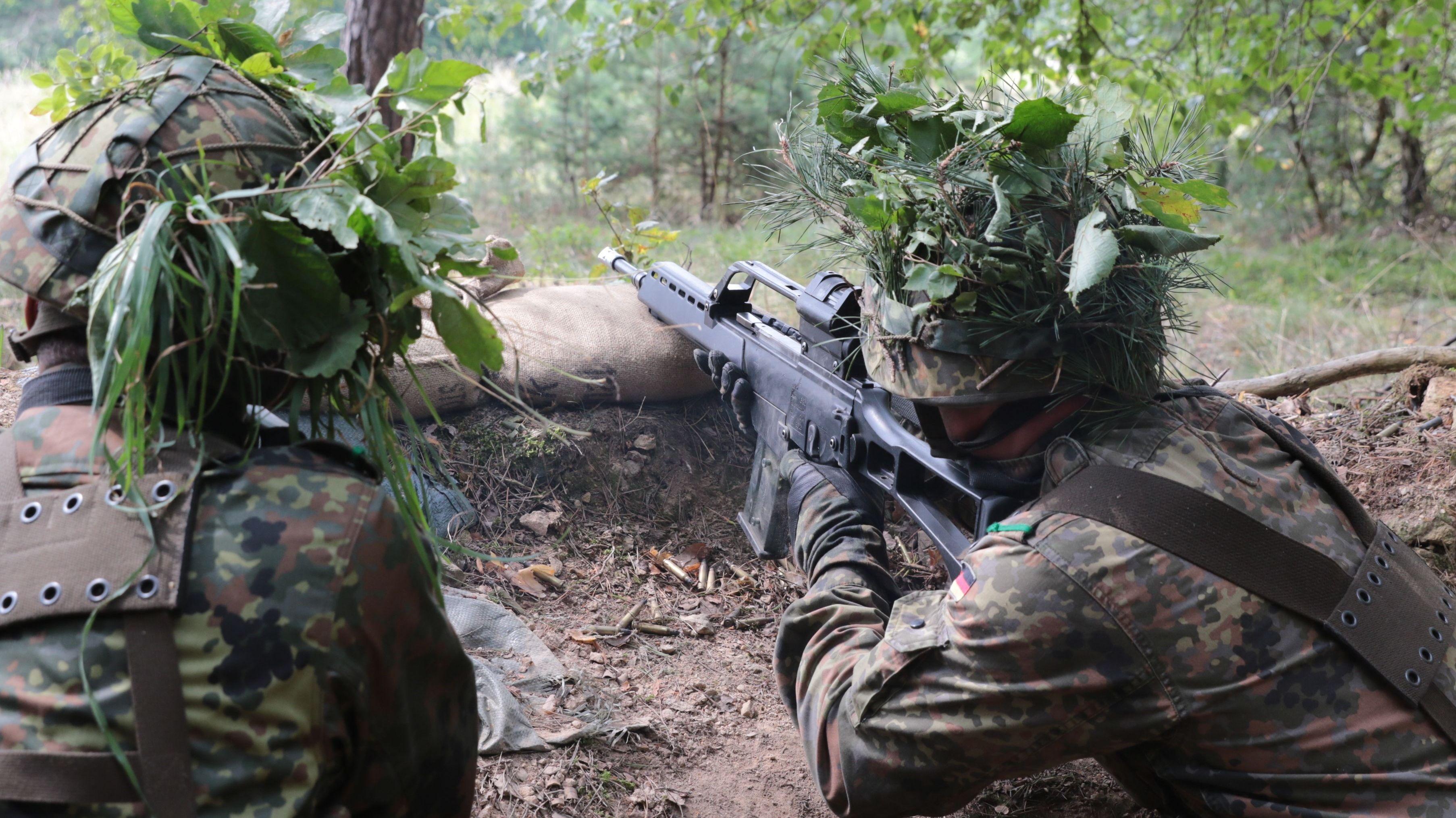 Zwei Reservisten von hinten, die mit einem Gewehr auf ein unbekanntes Ziel zielen.