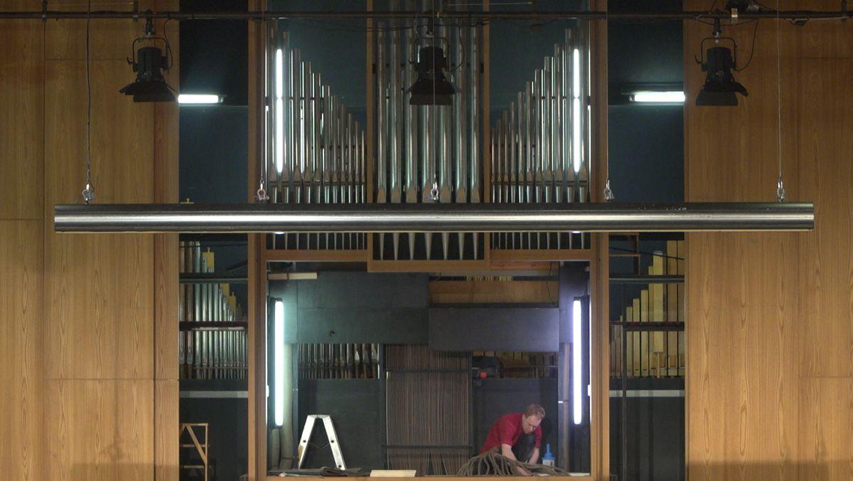 Ein Mann kniet vor der Orgel - er