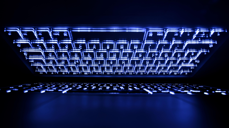 beleuchtete Tastatur eines Laptops spiegelt sich im Bildschirm