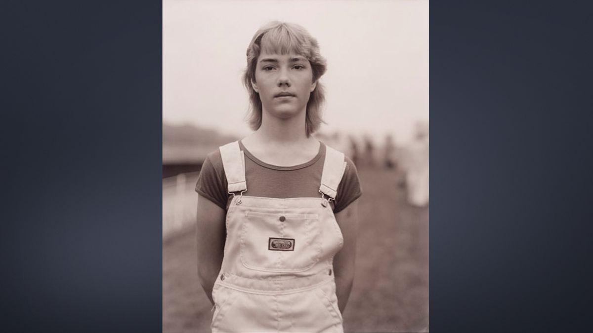 Schwarz-weiß Porträt einer jungen Frau in Latzhose und T-shirt: Aus der Porträt-Ausstellung der Pinakothek der Moderne