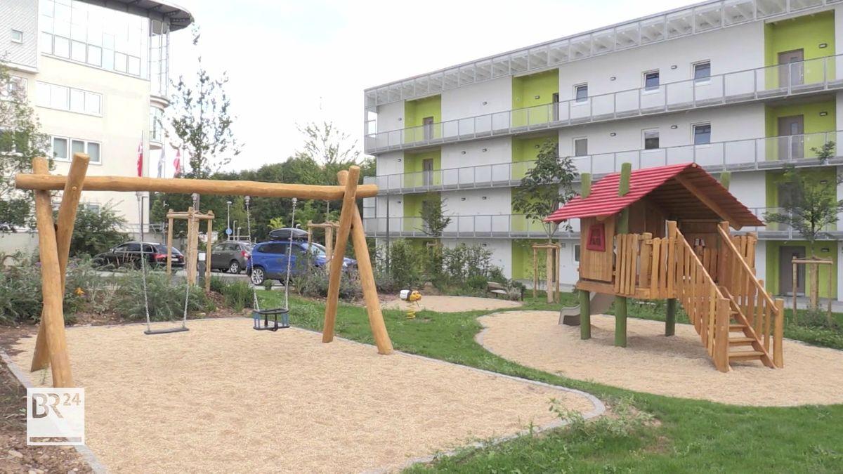 Ein Kinderspielplatz mit einer Holzschaukel, dahinter ein großes, dreistöckiges Haus mit den neuen Wohnungen.
