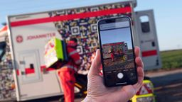 Handy vor Krankenwagen   Bild:Johanniter Unfallhilfe