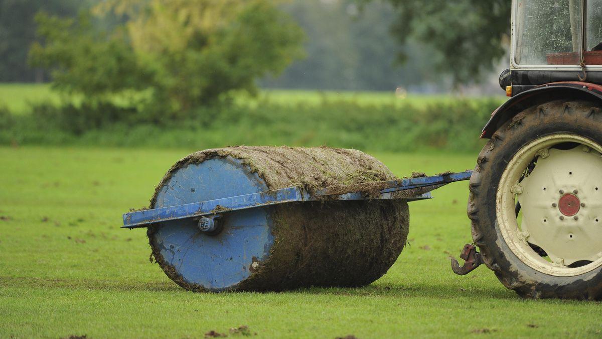 Ein Landwirt walzt eine Grünfläche.