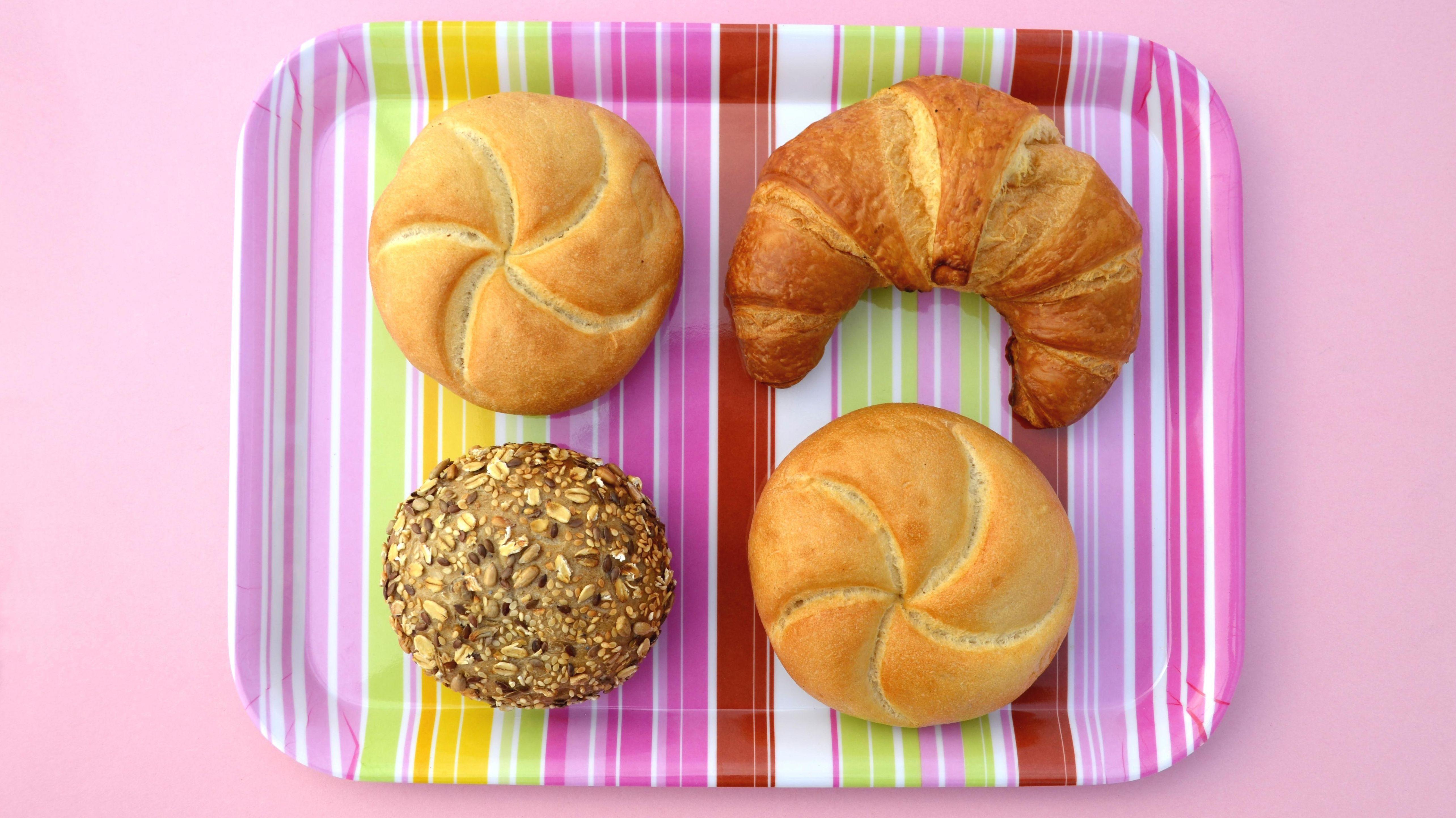 Semmeln und Croissant auf einem bunten Tablett