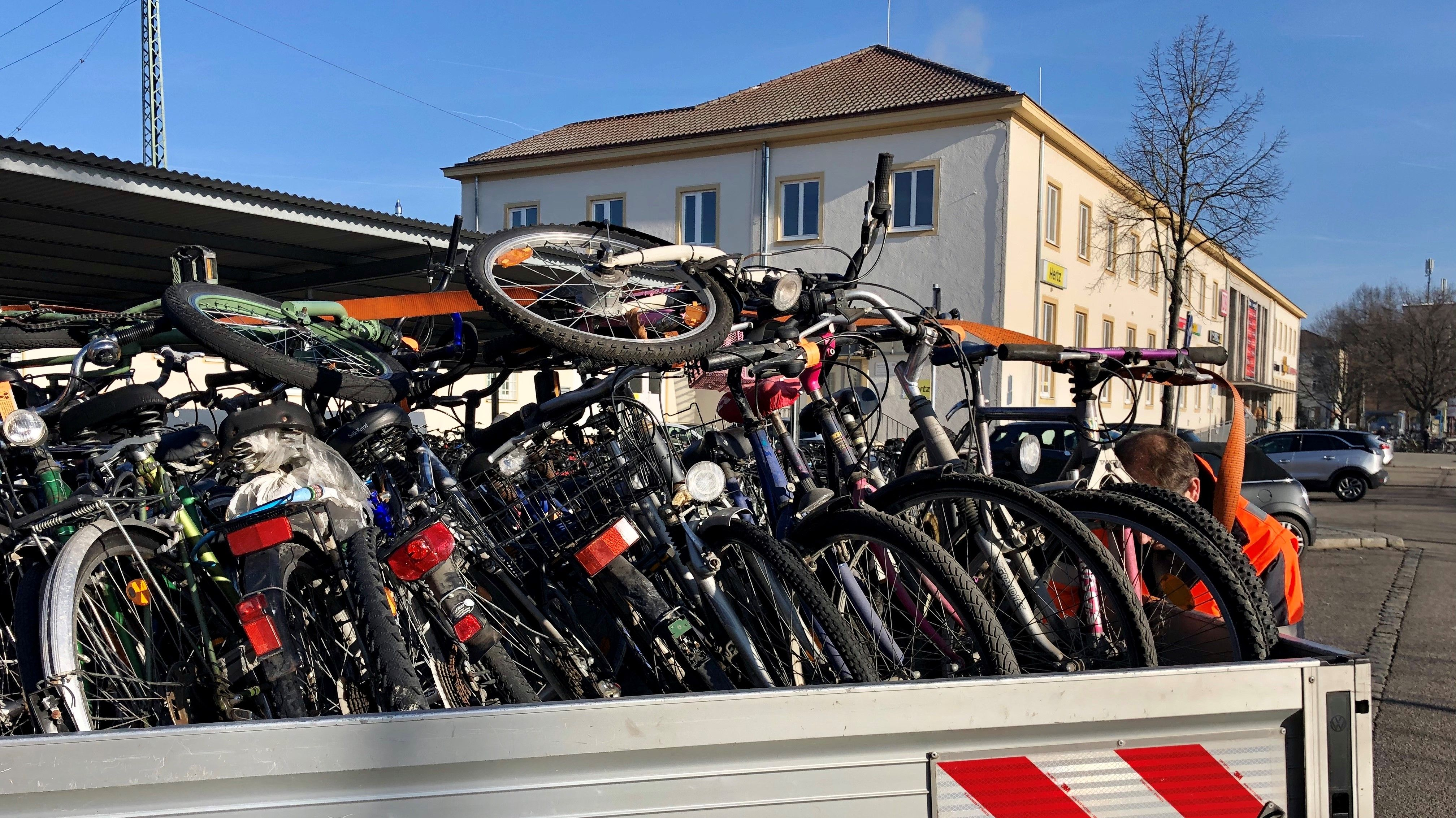 Schrotträder auf einem Anhänger vor dem Landshuter Bahnhofsgebäude