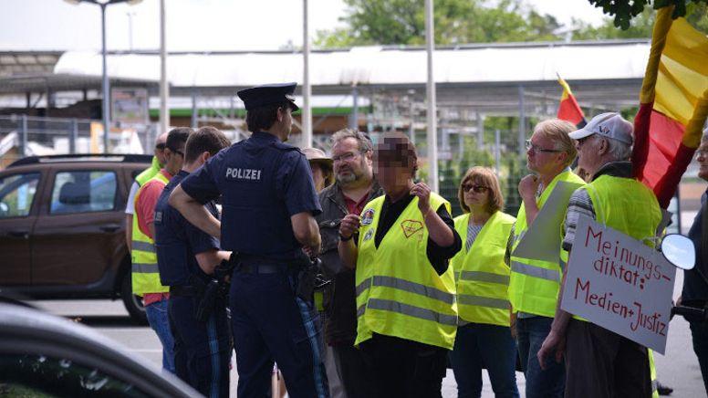 Marion G. (Mitte, gepixelt) im Gespräch mit einem Polizeibeamten (Archiv) | Bild:BR/Jonas Miller