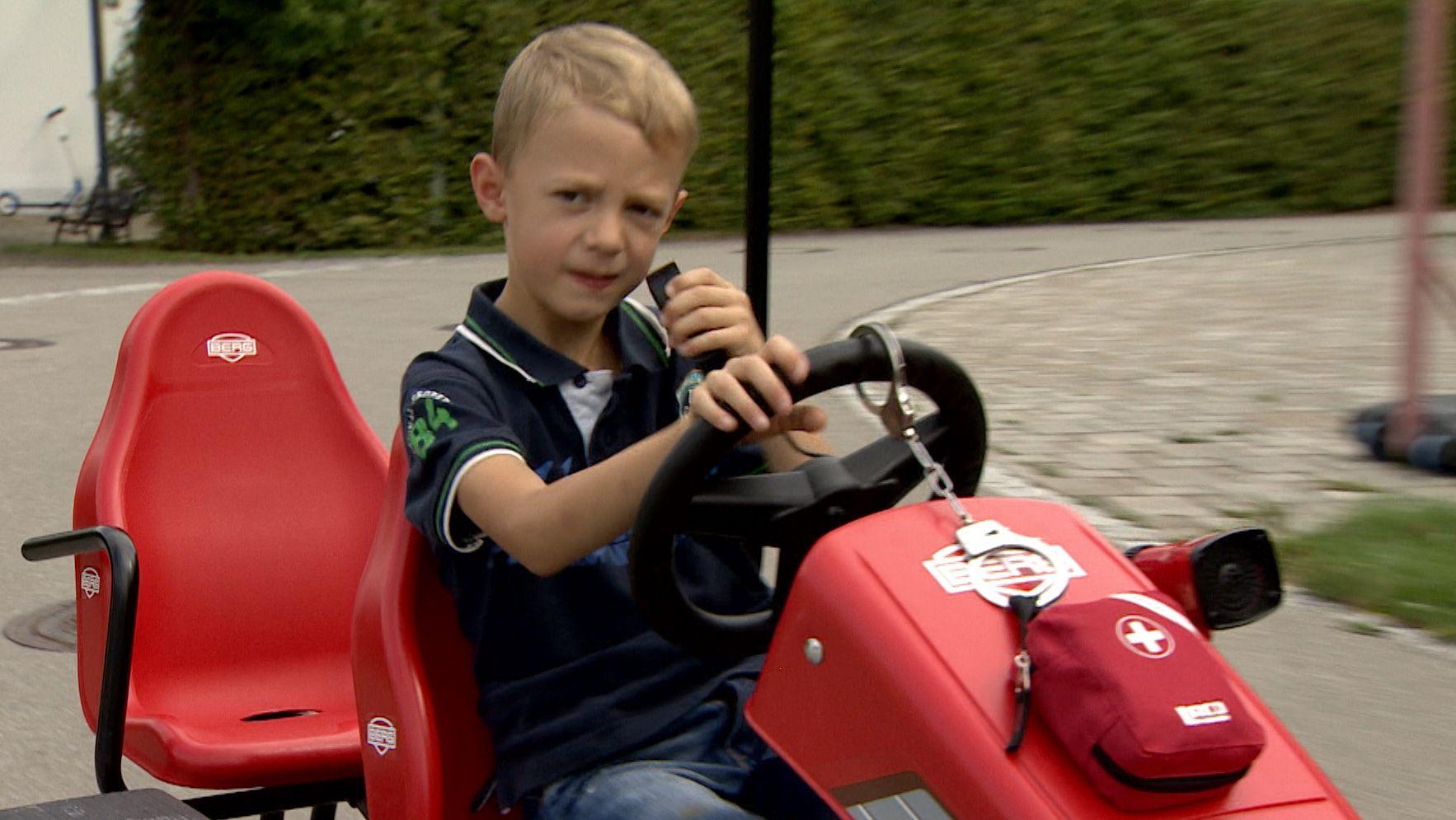 Junge sitzt auf rotem Kettcar
