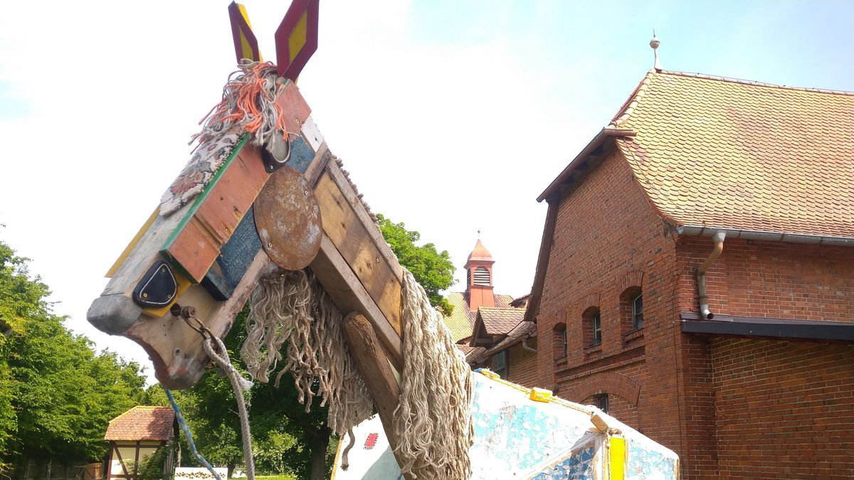 Ein hölzernes Pferd vor einem Gebäude des Wolfgangshofes